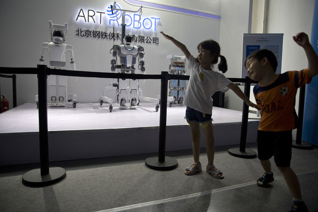 Children play near robots on display a day before the opening of the World Robot Conference held in Beijing, China, Tuesday, August 22, 2017. (Photo by Ng Han Guan/AP Photo)