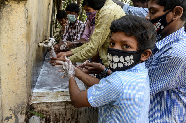 Students wearing facemasks wash their hands before attending a class at a governement-run high school in Secunderabad, the twin city of Hyderabad, on March 4, 2020, as part of health measures taken against the COVID-19 coronavirus outbreak. The new coronavirus that emerged in a Chinese market at the end of last year has killed 2,981 with more than 80,200 people infected in total, the National Health Commission said. (Photo by Noah Seelam/AFP Photo)