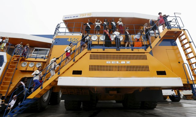 """Participants in the """"Mrs Universe 2015"""" contest pose for a photo at the Belarusian Autoworks (BELAZ) plant during their visit in Zhodino, Belarus, August 26, 2015. (Photo by Vasily Fedosenko/Reuters)"""
