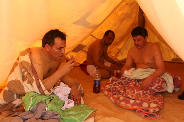 Patients drink herbal tea inside a tent used as a sauna as they relax after their sand bath in Siwa, Egypt, August 17, 2015. (Photo by Asmaa Waguih/Reuters)