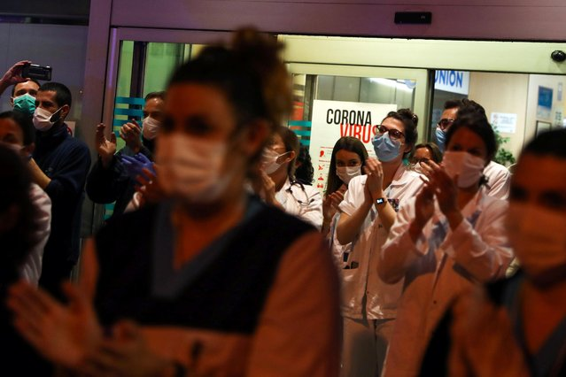 Medical staff from the Fundacion Jimenez Diaz hospital join neighbours applauding from their balconies in support for health workers, during the coronavirus disease (COVID-19) outbreak, in Madrid, Spain on March 23, 2020. (Photo by Susana Vera/Reuters)