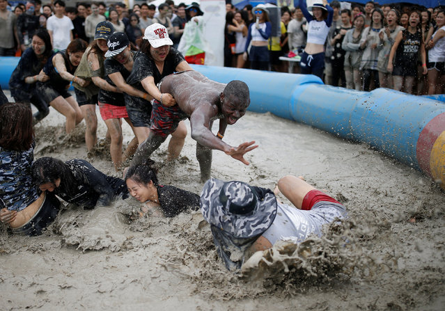 Tourists play in a mud pool during the Boryeong Mud Festival at Daecheon beach in Boryeong, South Korea, July 16, 2016. (Photo by Kim Hong-Ji/Reuters)