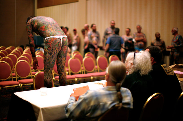 """Contestant Yoshi shows off the back of his full-body tattoo to judges at the National Tattoo Association Convention in Cincinnati, Ohio, on April 13, 2012. Yoshi, from Japan, was tattooed by Horiyoshi III and is a multi-award winning contestant in the world of full-body tattoos. In Cincinnati he won third place in the """"Best Tattooed Male"""" category. Picture taken April 13, 2012. (Photo by Jason Reed/Reuters)"""