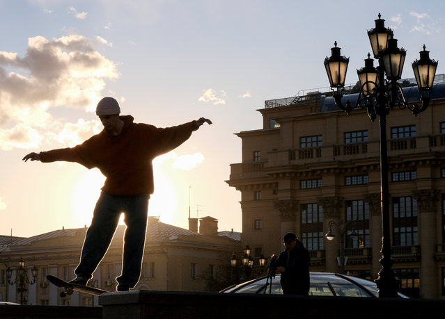 A skateboarder performs a trick in Manezh Square in central Moscow, Russia on March 19, 2020. (Photo by Evgenia Novozhenina/Reuters)