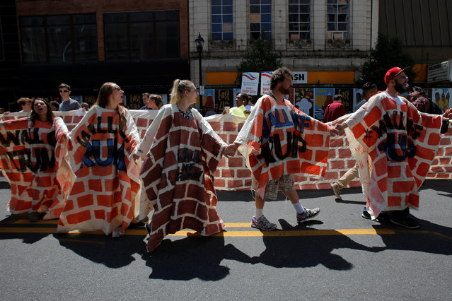 Demonstrators walk in a fake wall during protests outside the Republican National Convention in Cleveland, Ohio, U.S., July 20, 2016. (Photo by Andrew Kelly/Reuters)