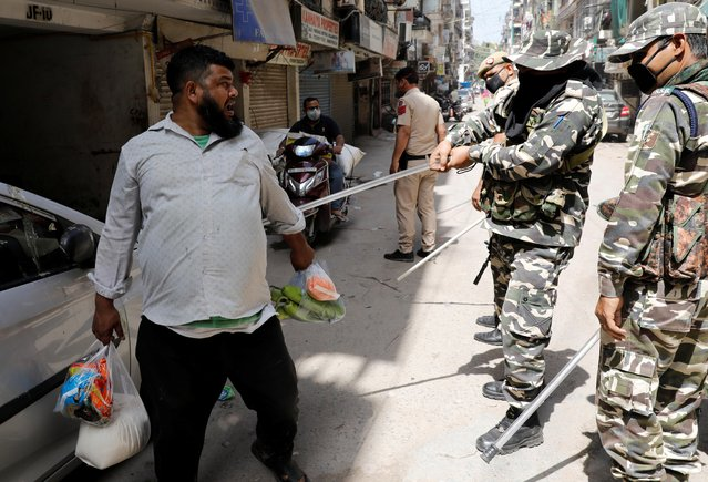 Police officers wield their batons against a man as a punishment for breaking the lockdown rules after India ordered a 21-day nationwide lockdown to limit the spread of coronavirus in New Delhi, India, March 25, 2020. (Photo by Adnan Abidi/Reuters)