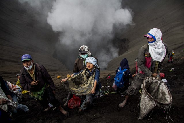 Indonesian Villagers use nets and sarong as they wait for offerings to be thrown by Hindu worshippers at the crater of Mount Bromo during the Yadnya Kasada Festival in Probolinggo, East Java, Indonesia, 21 July 2016. (Photo by Fully Handoko/EPA)