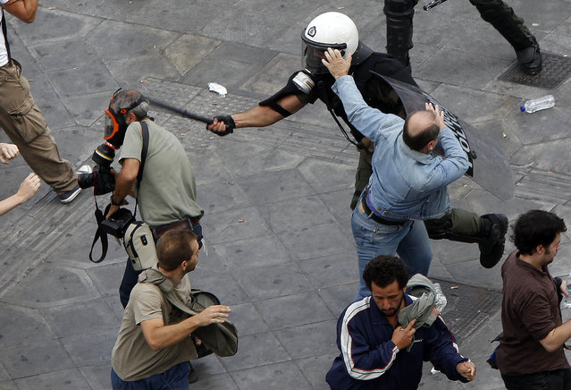Riot policeman uses his baton against news photographer Panagiotis Tzamaros, who is on assignment for AFP, during a demonstration in Athens' Syntagma (Constitution) square October 5, 2011. Tzamaros suffered light head wounds and bruises. (Photo by Yannis Behrakis/Reuters)