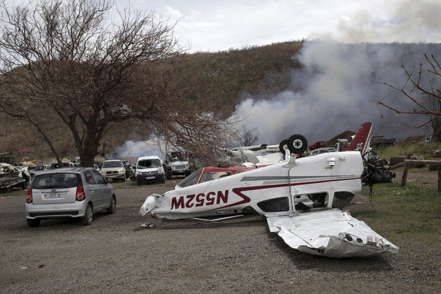 A small plane lays flipped over, one week after the passing of Hurricane Irma, at the airport parking lot on the outskirts of Gustavia, St. Barthelemy, part of the French Antilles, Monday, September 18, 2017. Hurricane Maria is passing far south of St. Barthelemy on Tuesday and charging into the eastern Caribbean that threatens islands already devastated by Hurricane Irma. (Photo by Enrico Dagnino via AP Photo)