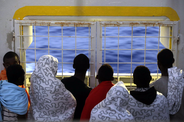 Migrants look at the sea as they crowd the bridge of the Norwegian Siem Pilot ship, Wednesday, September 2, 2015. The Siem Pilot is carrying to the Italian Port of Cagliari hundreds of migrants rescued in several operations in the Mediterranean sea. (Photo by Gregorio Borgia/AP Photo)
