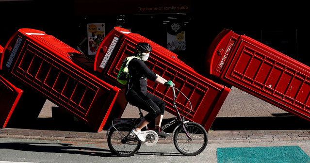 A person is seen riding a bicycle wearing face protection in front of an art installation called Out of Order while the spread of the coronavirus disease (COVID-19) continues, London, Britain, April 20, 2020. (Photo by Peter Nicholls/Reuters)