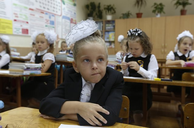 Students attend their first lesson of the day in a school in the southern coastal town of Mariupol, September 1, 2014. (Photo by Vasily Fedosenko/Reuters)