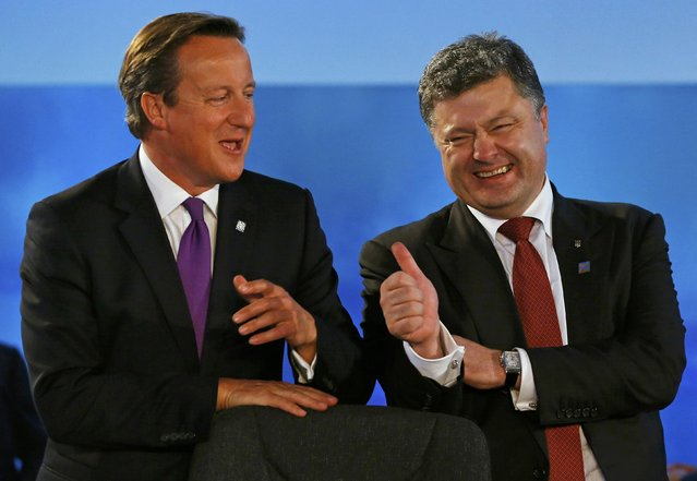 Britain's Prime Minister David Cameron (L) laughs with Ukraine's President Petro Poroshenko during the NATO summit at the Celtic Manor resort, near Newport, in Wales September 4, 2014. The resort is the venue for the two day NATO summit which started today. (Photo by Yves Herman/Reuters)