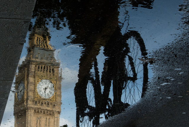 The Queen Elizabeth Tower (Big Ben) is reflected in a puddle as a cyclist rides by in London, on 27 June 2016. Britain began preparations to leave the European Union on Monday but said it would not be rushed into a quick exit, as markets plunged in the wake of a seismic referendum despite attempts to calm jitters. (Photo by Leon Neal/AFP Photo)