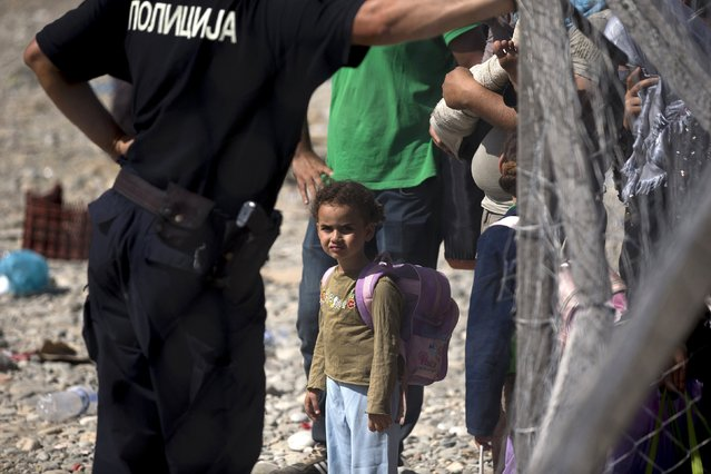 A migrant girl looks on next to a policeman as she waits to board a train after crossing the Macedonian-Greek border near Gevgelija, Macedonia, September 5, 2015. (Photo by Stoyan Nenov/Reuters)