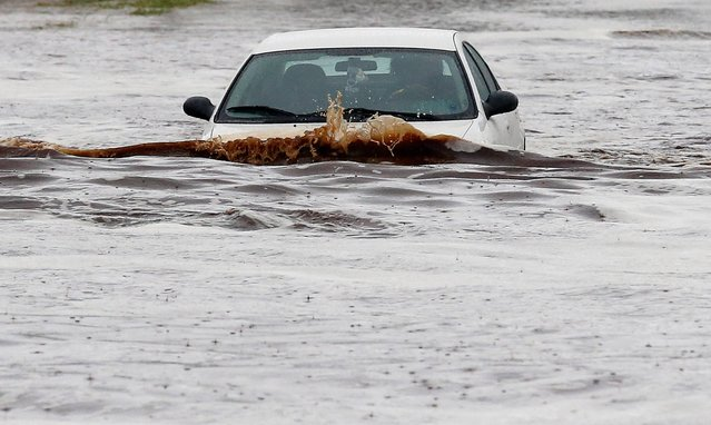 A driver tries to navigate a severely flooded street as heavy rains pour down Monday, September 8, 2014, in Phoenix. Storms that flooded several Phoenix-area freeways and numerous local streets during the Monday morning commute set an all-time record for rainfall in Phoenix in a single day. (Photo by Ross D. Franklin/AP Photo)