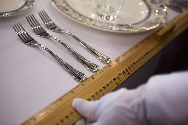 A student uses a ruler to measure the distance between forks before a formal dinner at The International Butler Academy China on September 16, 2014 in Chengdu, China. (Photo by Taylor Weidman/Getty Images)