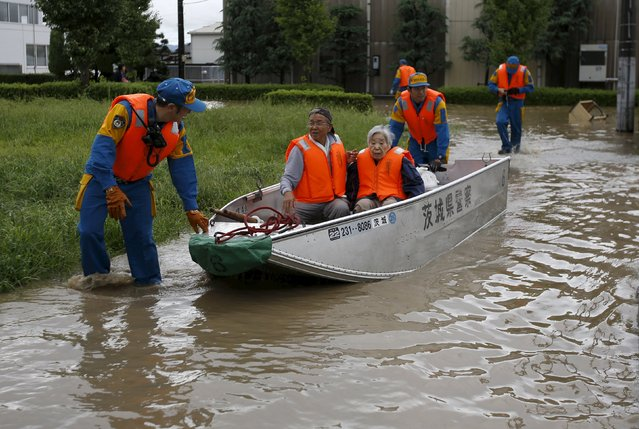 Residents are rescued by police officers at a residential area flooded by the Kinugawa river, caused by typhoon Etau, in Joso, Ibaraki prefecture, Japan, September 10, 2015. (Photo by Issei Kato/Reuters)