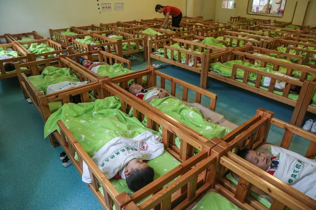 This photo taken on May 11, 2020 shows children sleeping after lunch at a kindergarten in Yongzhou in China's central Hunan province. China reported no new domestic coronavirus infections on May 12, after two consecutive days of double-digit increases fuelled fears of a second wave of infections. (Photo by AFP Photo/China Stringer Network)