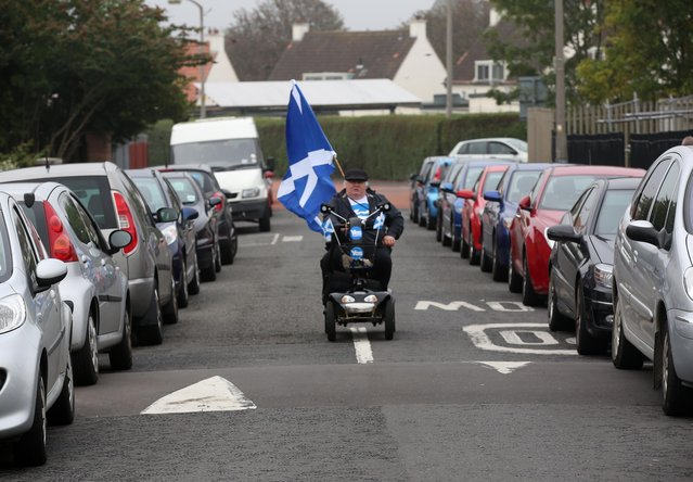 """A man riding a mobility scooter arrives to take part in a """"short walk to freedom"""" march in Edinburgh, Scotland September 18, 2014. Polling in the referendum on Scottish independence began on Thursday morning, as Scotland votes whether or not to end the 307-year-old union with the rest of the United Kingdom. (Photo by Paul Hackett/Reuters)"""