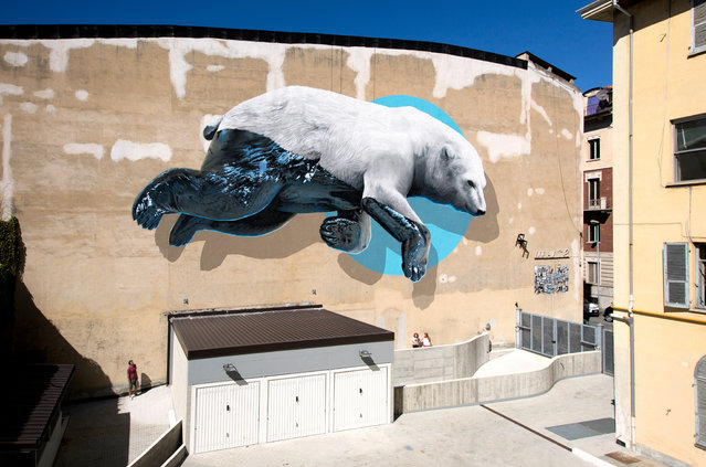 "A polar bear whose bottom half is caked in oily black gunk. A whale wrapped in striped fabric: a pseudo straightjacket. These are the messes climate change leaves behind, the things we know are happening but often don't have the opportunity to see with our own eyes. Swiss street art duo Christian Rebecchi and Pablo Togni, otherwise known as NeverCrew, met in art school when they were 15 and started making work together soon after. As a team, the artists adorn the world with eye-popping and gut-wrenching images depicting the consequences of humanity's actions on earth. Here: ""Black machine"" mural painting and installation on the Colosseo theater in Turin, Italy, in September 2015. (Photo by NeverCrew/The Huffington Post)"