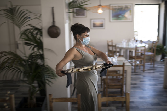 A waitress wearing a face mask to protect against  coronavirus carries out a plate of fish to serve at a seafood restaurant in Marseille, southern France, Tuesday, June 2, 2020. The French way of life resumes Tuesday with most virus-related restrictions easing as the country prepares for the summer holiday season amid the pandemic. (Photo by Daniel Cole/AP Photo)