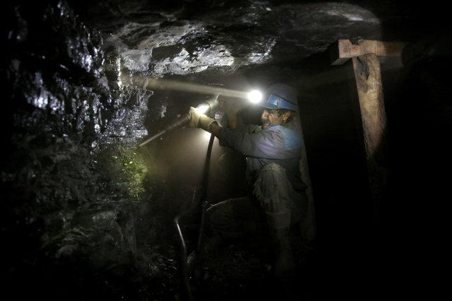 In this Monday, Aug. 18, 2014 photo, an Iranian coal miner works inside a mine near the city of Zirab 212 kilometers (132 miles) northeast of the capital Tehran, on a mountain in Mazandaran province, Iran. The miners tunnel deep into the mountains, working in dark, narrow passageways where the risk of toxic gases and cave-ins is never far from their minds. (Photo by Ebrahim Noroozi/AP Photo)
