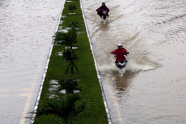 People ride motorcycles along flooded road after typhoon Damrey hits Vietnam in Hue city, Vietnam Vietnam on November 5, 2017. (Photo by Reuters/Kham)