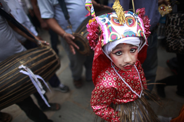 "A Nepalese Hindu boy in festival attire walks in a procession during ""Gai Jatra"", or Cow Festival in Kathmandu, Nepal, Friday, August 19, 2016. Members of Nepal's Newar Community celebrate the festival in memory of their family members who died the preceding year, believing that the cow will guide them in their journey to heaven. (Photo by Niranjan Shrestha/AP Photo)"