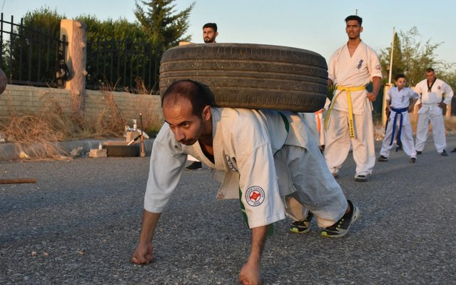 A group of Karate practitioners train under the supervision of katate coach Omer et-Timimi in Kirkuk, Iraq on May 30, 2020. Young people, whose schools have been on holiday for about two months due to the coronavirus pandemic, come together three days a week and strengthen their immunity with karate sport. (Photo by Ali Makram Ghareeb/Anadolu Agency via Getty Images)