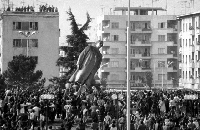 Hundreds of Albanians push over the bronze statue of the late communist dictator Enver Hoxha located in the central square of Tirana, February 20, 1991. Thousand others cheer from the roofs of the buildings as the last symbol of the communist dictatorship is forcefully removed. A rally was organised February 20 by the opposition to commemorate the 9th anniversary when Albanians toppled the statue of the late communist dictator Enver Hoxha from Tirana's central square. (Photo by Lulzim Lika/Reuters)
