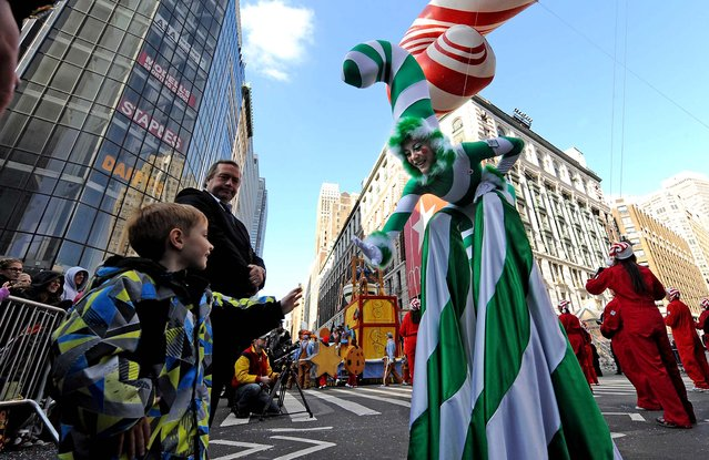 A Candy Cane girl reaches out to a child at Herald Square during the 86th annual Macy's Thanksgiving Day Parade. (Photo by Louis Lanzano/Associated Press)