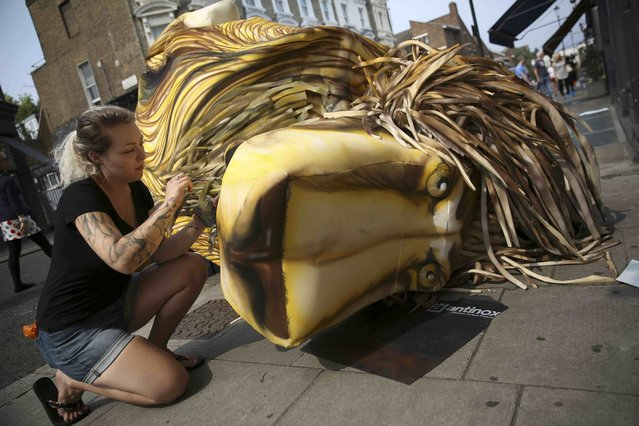 A woman decorates a lion head which will form a float at the Notting Hill Carnival in London, Britain August 27, 2016. (Photo by Neil Hall/Reuters)