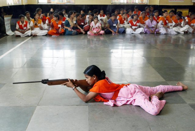 Women activists of the Vishwa Hindu Parishad or World Hindu Council, ahardline Hindu organisation, train in the art of shooting during asummer training camp, in Bombay May 17, 2003. (Photo by Sherwin Crasto/Reuters)