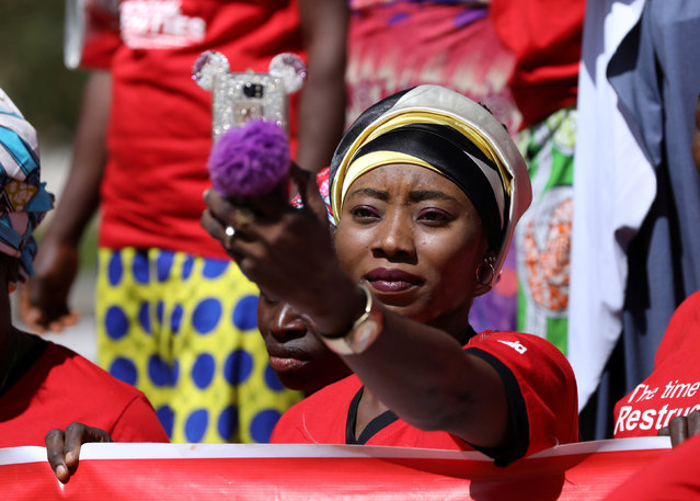 A woman takes a selfie during a women's rally organised by ActionAid, for FCT communities, demanding social economic empowerment, at the Unity Fountain in Abuja, Nigeria December 5, 2017. (Photo by Afolabi Sotunde/Reuters)