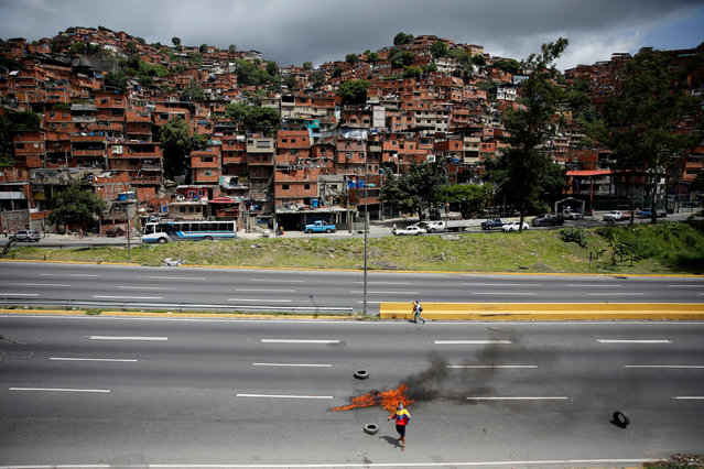 """A protester dressed in a jacket with the national colours stands next to a burning roadblock during a rally against Venezuela's President Nicolas Maduro's government in Caracas, Venezuela, June 26, 2017. Ivan Alvarado: """"The street was open and empty a little while before I took this picture. The man wearing the Venezuelan flag jacket brought the tyres to the middle of the highway and set them alight. For me the highway in this image acts like a imaginary border that divides two realities in Caracas – behind me was the chaos and tear gas at the rally and across the other side of the road a quiet scene of the houses stacked up on the hill"""". (Photo by Ivan Alvarado/Reuters)"""
