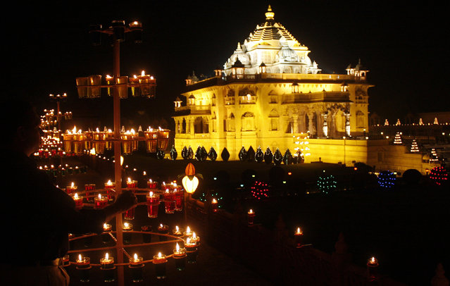 A devotee (L) lights a lamp at Akshardham temple during celebrations to mark the annual Hindu festival of Diwali at Gandhinagar in Gujarat October 17, 2009. (Photo by Amit Dave/Reuters)