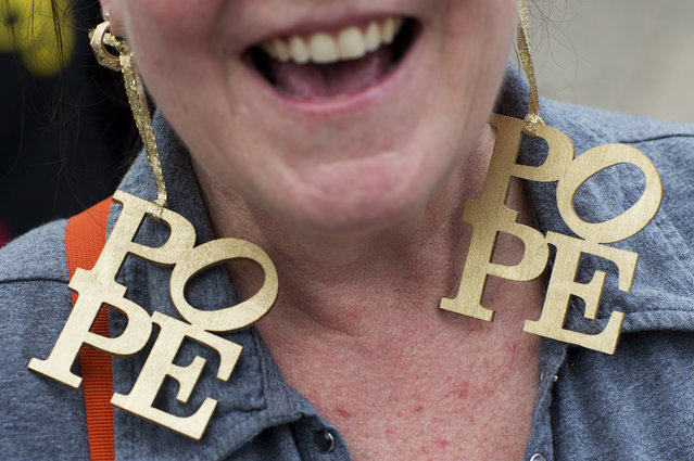 Marie Eveleth, of Washington, N.J., wears earnings that spell out 'pope' as she sells them to pedestrians around City Hall before Pope Francis comes through the area for a parade Saturday, September 26, 2015, in Philadelphia. (Photo by David Goldman/AP Photo)