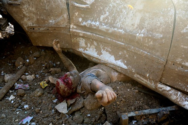 An injured man is pictured under a vehicle following an explosion in Beirut's port area, Lebanon on August 4, 2020. When Reuters photographer Mohamed Azakir saw a man pinned under a vehicle, covered in a thick film of rubble and blood, he thought the man was dead. But then the man opened his eyes and began waving his arms and asking for help. Azakir called over some rescuers who were nearby. In a series of photographs, he recorded the rescue of the man, while also helping the rescuers move the car to free him. (Photo by Mohamed Azakir/Reuters)