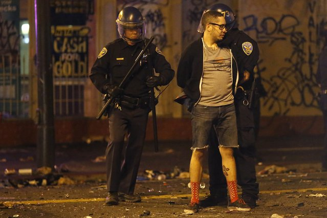 A man is being detained by the police after a street celebration in San Francisco, California October 29, 2014. (Photo by Stephen Lam/Reuters)
