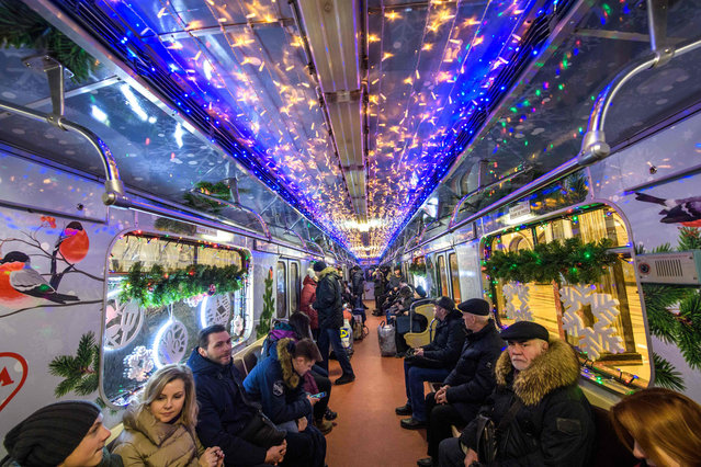Passengers sit inside a New Year decorated metro train in Moscow on January 2, 2018. (Photo by Yuri Kadobnov/AFP Photo)