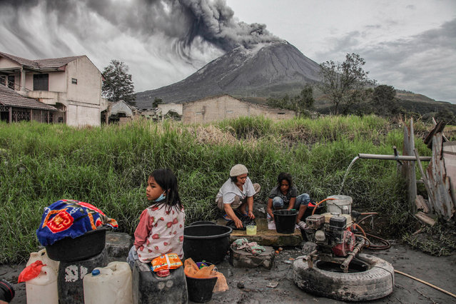 """Villagers do their laundry as Mount Sinabung spews volcanic materials during an eruption, in Karo, North Sumatra, Indonesia  on August 14, 2020. Sinabung is among more than 120 active volcanoes in Indonesia, which is prone to seismic upheaval due to its location on the Pacific """"Ring of Fire"""", an arc of volcanoes and fault lines encircling the Pacific Basin. (Photo by AP Photo/Rex Features/Shutterstock)"""