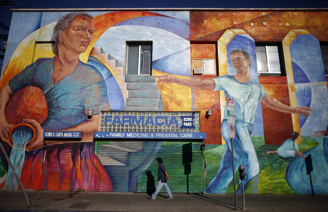 A man walks past a mural in the Echo Park area of Los Angeles, home to many Mexican and Central American migrants, in California August 5, 2014. Los Angeles is a culturally thriving city and one of the most ethnically diverse in the United States, with a population that is 48.5 percent Latino and 11.3 percent Asian, according to a 2010 census. (Photo by Lucy Nicholson/Reuters)