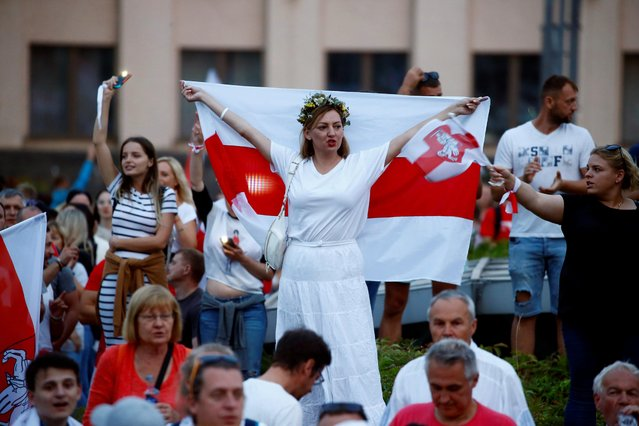 A woman holds a historical white-red-white flag of Belarus as she attends an opposition demonstration in Independence Square in Minsk, Belarus on August 18, 2020. (Photo by Vasily Fedosenko/Reuters)