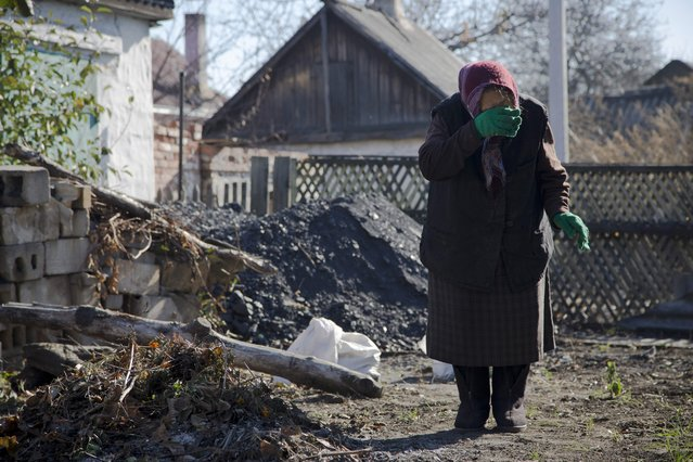 In this photo taken on Tuesday, October 28, 2014, Lyubov Stasovskaya, 86 wipes tears in the backyard of her house in the town of Donetsk, eastern Ukraine. (Photo by Dmitry Lovetsky/AP Photo)