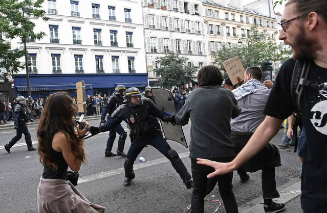 Policemen clash with protestors during a protest against the controversial labour reforms of the French government in Paris on September 15, 2016. French riot police fired teargas and stun grenades on September 15, 2016 during clashes in Paris with opponents of labour reforms who threw molotov cocktails, the latest outbreak of violence over the controversial new laws. Twelve people were arrested in the capital, where around 13,000 people took part in the rally against measures aimed at loosening France's notoriously rigid employment laws, the 14th such demonstrations in six months. (Photo by Christophe Archambault/AFP Photo)