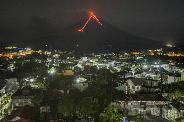 Lava cascades down the slopes of the Mayon volcano seen from Legazpi city, Albay province, 340 kilometers (210 miles) southeast of Manila, Philippines, Tuesday, January 16, 2018. (Photo by Dan Amaranto/AP Photo)