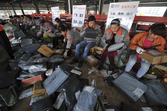 Employees sort packages at a hub of Shentong (STO) Express delivery company in Hefei, Anhui province, November 12, 2014. China's Singles' Day, which is celebrated annually on November 11, has become the world's largest online shopping day, with online shopping websites offering attractive discounts. (Photo by Reuters/Stringer)
