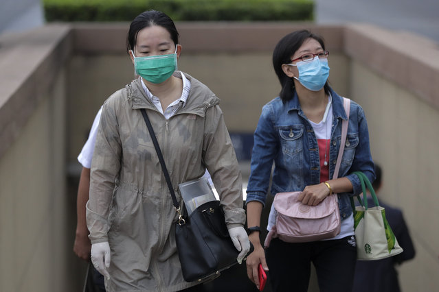 Women wearing face masks to help curb the spread of the coronavirus walk out from a subway station in Beijing, Tuesday, September 15, 2020. Even as China has largely controlled the outbreak, the coronavirus is still surging across other parts of the world. (Photo by Andy Wong/AP Photo)