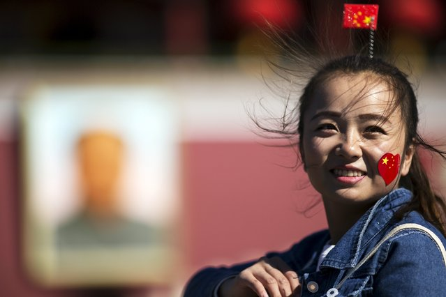 A young woman with a sticker and a hairpin in national colours poses for pictures at Tiananmen Gate as people celebrate National Day marking the 66th anniversary of the founding of the People's Republic of China in Beijing October 1, 2015. (Photo by Damir Sagolj/Reuters)